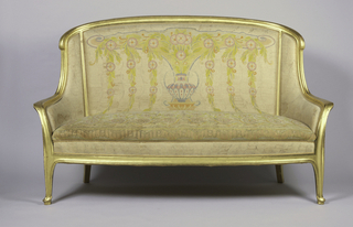 "Closed arm upholstered sofa with exposed frame which is contour-edged and gilded. Slightly arched and curved back rail with down-curved ""ears""; out-curving arms; exposed narrow vertical supports between back and seat rails; two front legs terminate in gently pointed contour-edged feet on small supports; two square rear legs which curve outward and have slight molding on the outer surface. Multicolored pastel silk needlepoint upholstery on ivory ground depicting vase, round stylized flowers, leaves and vines."