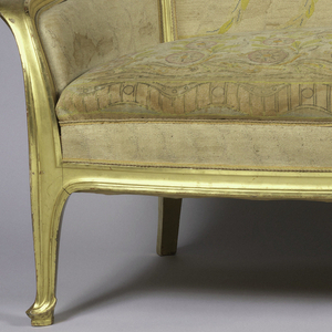 """Closed arm upholstered sofa with exposed frame which is contour-edged and gilded. Slightly arched and curved back rail with down-curved """"ears""""; out-curving arms; exposed narrow vertical supports between back and seat rails; two front legs terminate in gently pointed contour-edged feet on small supports; two square rear legs which curve outward and have slight molding on the outer surface. Multicolored pastel silk needlepoint upholstery on ivory ground depicting vase, round stylized flowers, leaves and vines."""