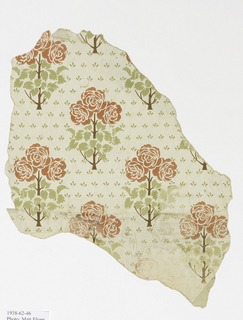 Drop-repeating pattern suggestive of stenciled decoration. Conventionalized rose-tree with three flowers; ground sown with staggered rows of clustered green strokes suggesting fleurs-de-lys.  Printed in green, pink and brown on white ground.