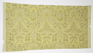 Damask pattern in cream and beige over gold background on textured paper.