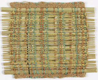 Sample for a window blind with a warp of green thick slubbed cotton, coral bouclé yarn, plaited silver tinsel, and gold-wrapped silk-core yarn. The weft employs cane in various thicknesses, with the thicker ones cut in half, and some yellow slubbed cotton, and plaited flat gold strips.