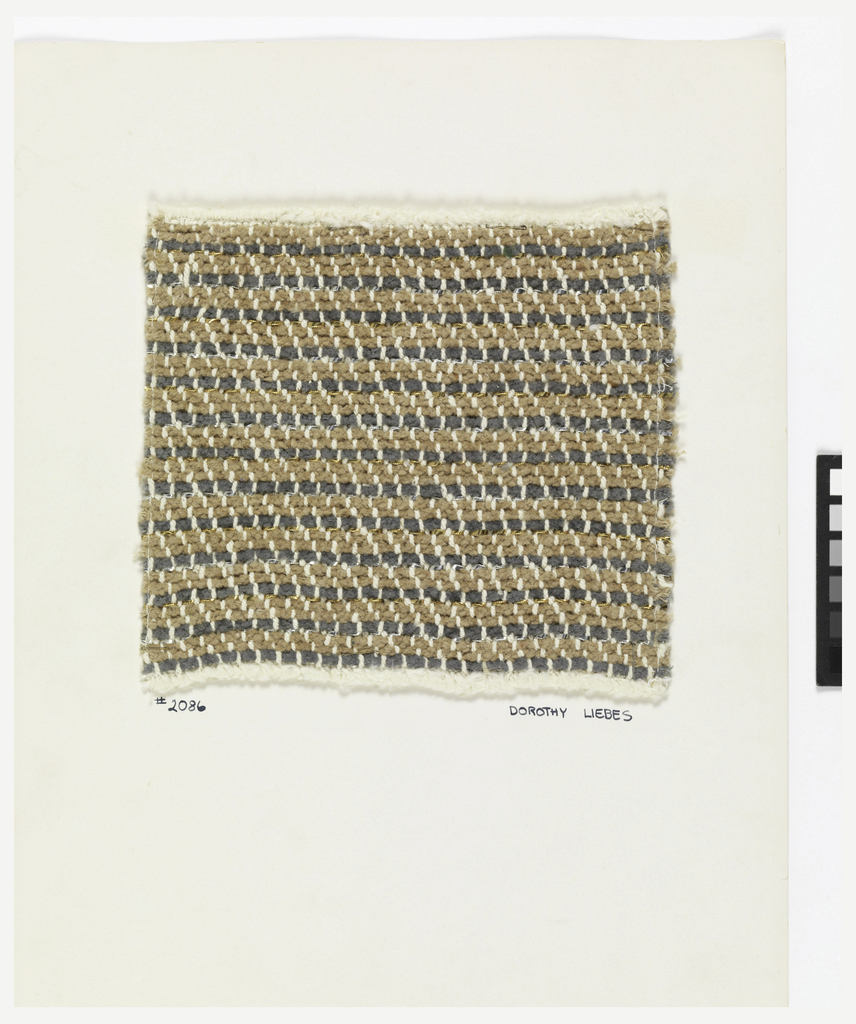 Woven sample mounted on cardboard card with notations made by the designer. Narrow horizontal stripes of tan and grey chenille are set off by alternating gold and silver metallic strips with a thin round wrapped-core yarn laid in on top of it. The warps are thick white cotton.