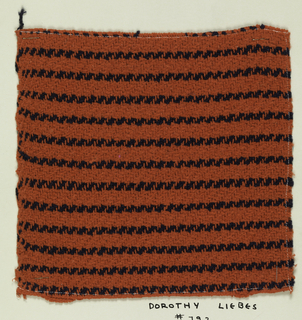 Woven sample mounted on a cardboard card with notations by the designer. Red chenille with narrow horizontal stripes of black bouclé yarn. Warps are red cotton; wefts are red chenille and black bouclé.