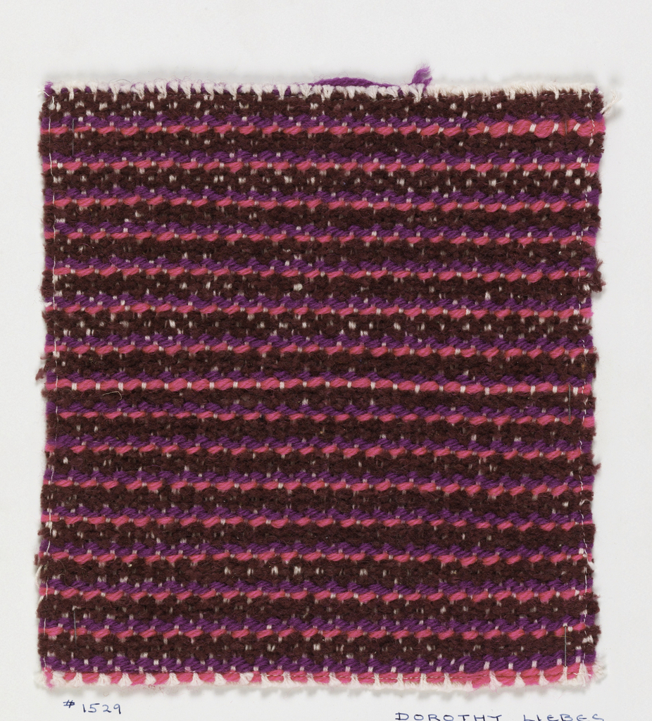 Woven sample mounted to a cardboard card with notations by the designer. Narrow horizontal stripes in dark red, pink and violet. Warps are white cotton; wefts are deep red cotton chenille, pink wool and violet wool.