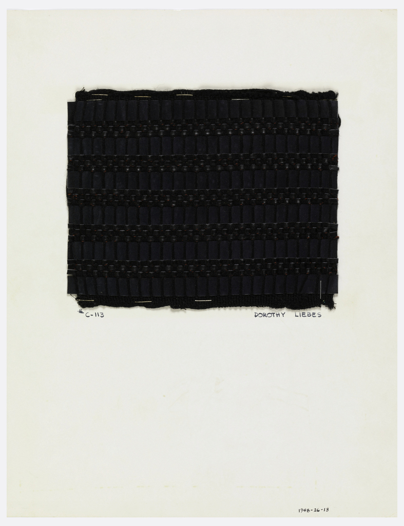 Woven sample mounted to a cardboard card with notations by the designer. Black fabric with horizontal bands of different textures. Warps are black wool; wefts and red and black silk and wool yarn, suede and leather strips. The wide suede strips float over grouped warps, giving a ribbed effect, which alternates with plain weave in the polished leather strips.