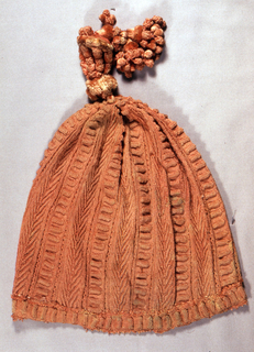 Cap of coral silk with a chenille tassel in the same color. Knit with altnernating bands in a simple goemetric patterns.