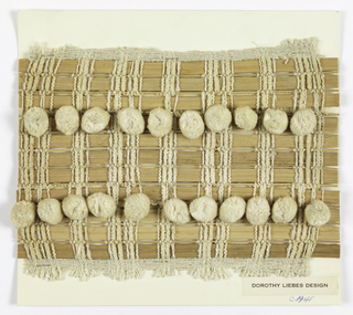 Plain weave with grouped warps consisting of white chenille, white boucle, and white plied yarn. Wefts are alternating rows of flat and round reeds. Flat reeds are occasionally paired with woven, ball fringe tape.