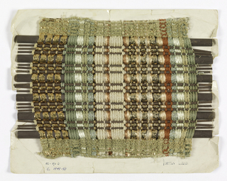 Window blind sample with paired and other multiple warps in three different shades of green and beige chenille, green boucle, brown boucle, beige plied yarn, two different brown smooth yarns and flat, metallic gold braid and metallic gold braided over two central cores. Wefts are a repeating sequence of one large brown half round and three narrow brown reeds.