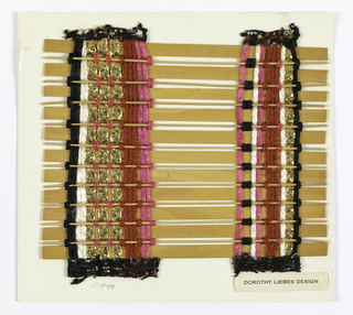 Two bands of warp threads form two vertical stripes in a random pattern of red chenille, pink and white yarn, black chenille and flat metallic gold braid. Weft has thin reeds alternating with flat reeds.