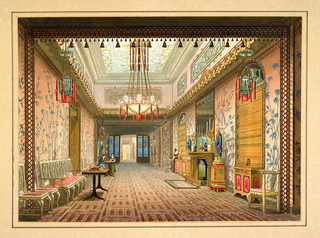 A view of an interior hallway highly decorated in Japoniste style. Large chandelier at center and two smaller lanterns have hanging red tassels. A fireplace on right wall with gold candelabra, flanked by two large red and green pedestals carrying two statues of figures in blue robes. Wall coverings are pink with blue stylized bamboo silhouettes. Chairs line the wall on left. Two figures are seated conversing while a third is knocking on or opening a door at right.