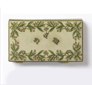 """Pocket book with embroidered cover. Cover on one side shows initials """"S.A.M."""" within a floral border. On the other, the word """"Souvenir"""" and four arrows with flowers and ribbons within border working on fine silk canvas. Lining is white satin. Satin covered book of white paper and pencil held in place by four satin straps that are fitted inside the pocket book."""