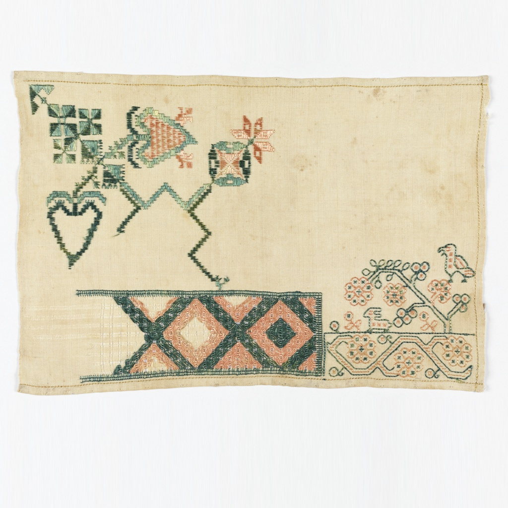 Lozenge design in drawnwork; embroidered bird, rabbit and plant forms.