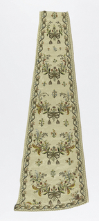 Long, narrow shaped panel, probably from a skirt, that is narrower at the top and curved at the bottom. Cream-white twill weave with brocading in a small floral design. Embroidered in multicolored silks, metallic threads and paillettes. Narrow borders and festoons of flowers extend across the panel, each caught with a ribbon and tassels in metallic thread.