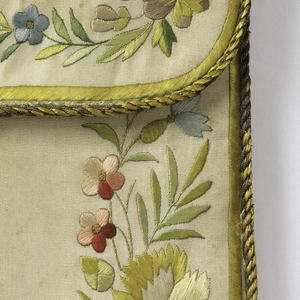 "Flat envelope-shaped case, probably for letters. Embroidered in colored silks and metal thread. Border of flowers. On flap, ""Souvenir D'Amitie"" in gold. On back, initials ""M.M."" in gold. Bound in gold. Button and loop."
