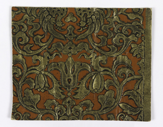 Imitation leather. Scrolling foliage design printed in terra cotta, gold and black on relief paper.