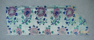 Pale blue satin ground with design of alternating chysanthemum and one other flower arranged in horizontal rows. Design in weft of blue, green, purple, and pink silk.