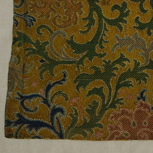 Yellow satin ground. Closely-spaced all-over design: elaborately scrolling leafy branches and decorative blossoms, in polychrome silk wefts. Very closely woven heavy fabric, started or stiffened on the back. Incomplete right selvedge.