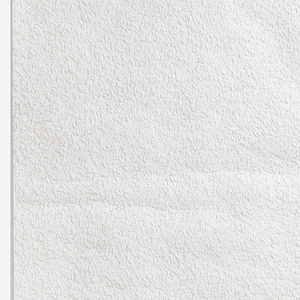Textured wallpaper, white, made of recycled paper and wood chips. Provides a plaster-like surface.