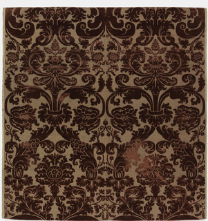 Length of voided red silk cut-pile velvet on a twill ground embellished with metal threads. Symmetrical esign of flowering branches forming a loose ogival framework containing large lotus-like blossoms. Modern adaptation of a 17th century style pattern.
