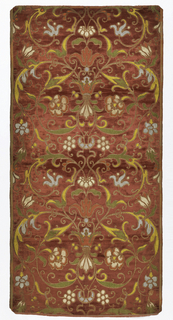 Woven design intended to look like Renaissance applique and embroidery. Vertically symmetrical pattern of flowers and leafy scrolls in blue, pink, yellow, green, cream and metallic gold on a raspberry red velvet ground.