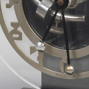 Clock face of glass for viewing gears with metal plate in shape of numbers over glass, resting on stepped black platform.