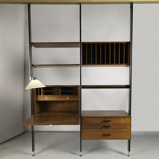 Structure composed of eighteen separate parts: three vertical poles with tracks forming two column units, into which triangular metal brackets are inserted, in the left hand column to hold up shelves and a fall-front teak desk unit with two interior drawers, and cubby holes, the flap opening with an ivory pull, two shelves above. A plastic cone-form lamp with stainless elbow joint, slides into the left hand column as a desk reading lamp. The right hand column has a shelf with teak dividers for record albums or folios, over a shelf with drop metal band to hide a fluorescent light bulb, over a three-drawer chest unit supported by black painted iron bars inserted into the metal columns, the drawers with ivory pulls matching the desk.