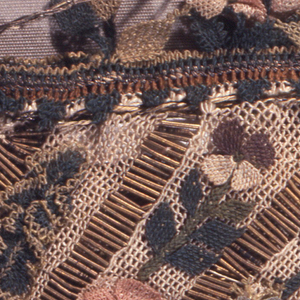 Drawstring bag with large metal tassel at bottom. Diagonal bands of white netting separated by bands of metallic purl. Bebilla flowers and fruit applied along netting and in a deep border at the top.
