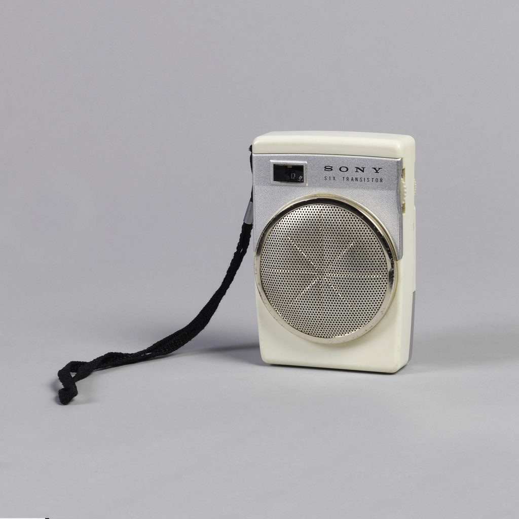 "Small rectangular white plastic body; front with white metal panel with station indicator, ""SONY"" logo and ""SIX TRANSISTOR,"" above large, circular, gold-toned pierced metal speaker with recessed asterisk-shaped design; black strap handle on left side; two small white control dials on right side; hinged white metal battery compartment in lower rear."