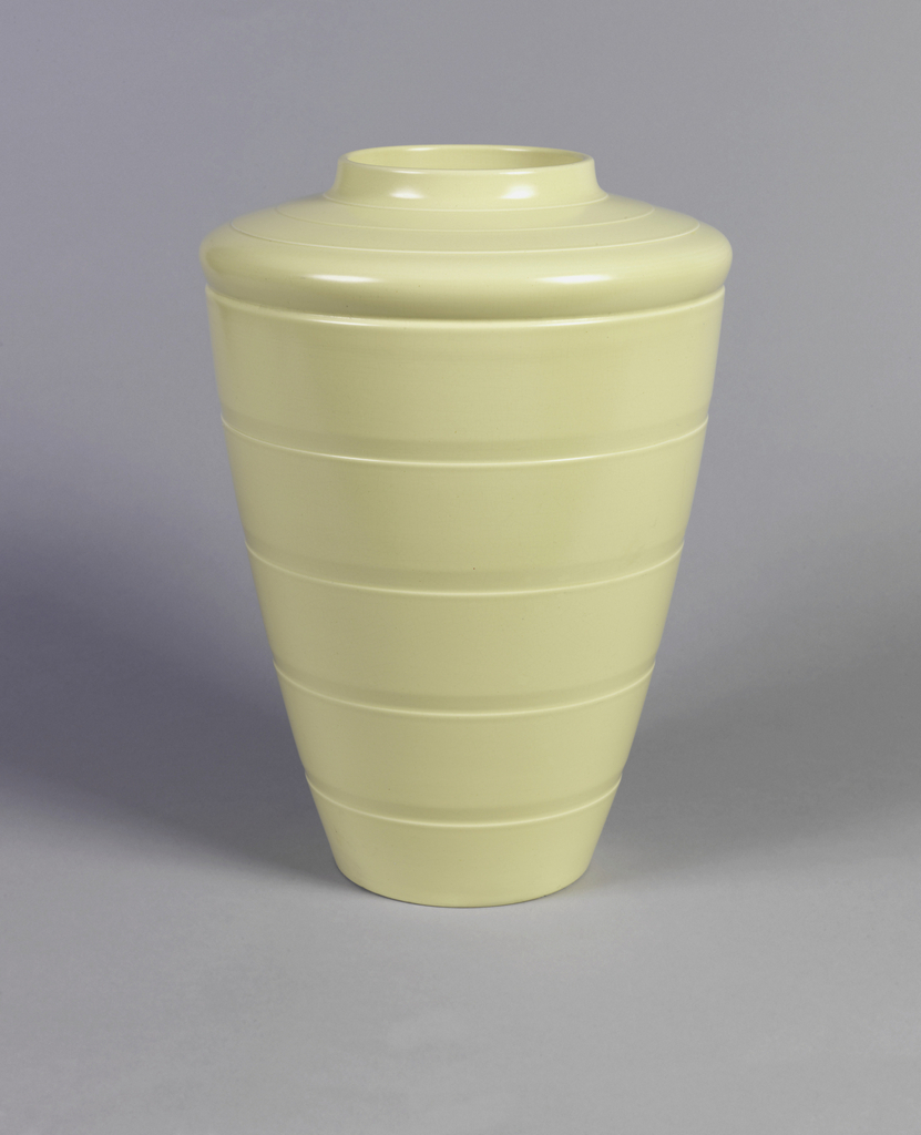 Tapering cylindrical form with circular mouth, broad shoulder; body decorated with horizontal grooves; creamy yellow matte glaze.