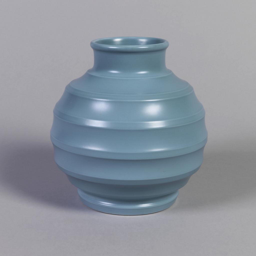 Globular form with circular mouth, short neck, circular foot; horizontal ridges throughout body; blue-green matte glaze.