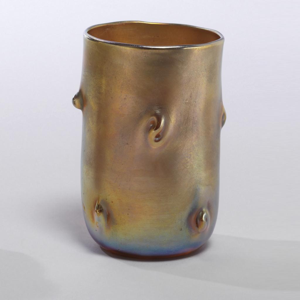Straight beaker, rounded at bottom. On sides, tooled irregular nubs. Greenish-gold iridescence.