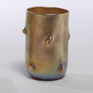 Straight beaker, rounded at bottom. On sides, tooled irregular nubs. Greenish-gold iridescence.