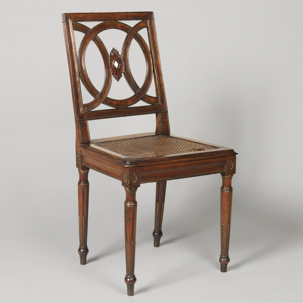 Open square back with design of one full and two half-circles interlocked, with a pierced cartouche at the mid-point.  Straight moulded seat rails, caned seat.  Legs are round, straight, tapered, and with reeded flutes.  Caned seat with hole in frontmost right corner.