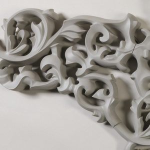 Form composed of three scrolling, foliate, grey polyconcrete modules (two small single modules flanking one large central module); flexible pipes extending from top and bottom of center section; tap attached at right side.