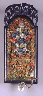 Within the glazed wooded frame which is crested with pierced scrollings and foliations is enclosed a quill-work composition of scrolls and flowers, roses, tulips, carnations, etc. in a vase. A siler bracket at the base receives the S-curved arm which terminates in candle-holder and drip pan.