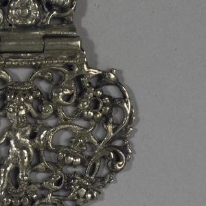 Two hinged parts of heart-shaped clasp, relief decorated with scroll and openwork and putti; single piece identical to hinged parts.
