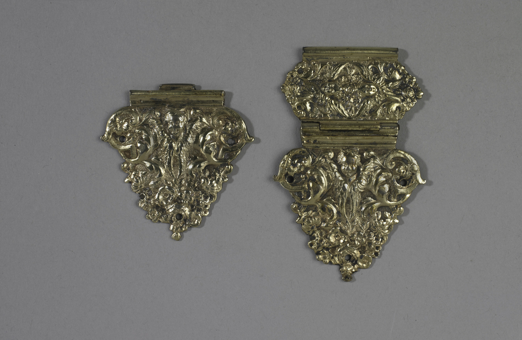 Two hinged parts of triangular clasp, relief decorated with scroll and openwork and putto head with wings; single piece identical to hinged part.