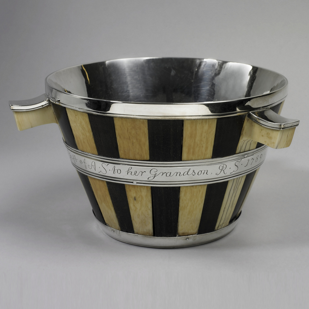 """Truncated cone-shaped bowl of silver, the outside covered with vertical staves of ebony and ivory alternating, interrupted by band inscribed with: """"The Gift of AS to her Grandson RS 1789."""" Three handles set horizontally."""