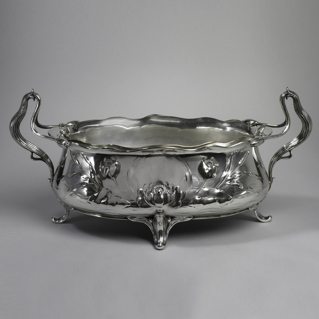 Jardiniere in silver repoussé with two ribbed upturned plant-like looped handles and four feet; scalloped rim and decorated with three blossoms on front.