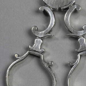 Scissors-type nippers, the arm composed of interlocking scrolls, terminating in shell-shaped ends. Circular swing-joint at center; engraved. Scroll handles with shaped finger loops.