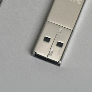 "Flash drive in the form of a key with a circular bow having large circular hole at top, vertical line decoration with ""LACIE"" logo in oval; simple flat shank with USB connector at bottom."