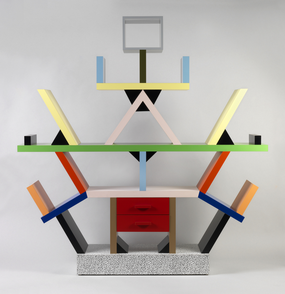 Colorful symmetrical, geometric sideboard, made up of three levels/shelving units of various sizes and central grounded 2-drawer sideboard on a stand. Each level has various diagonal units for storage that radiate from the central sideboard; all topped with a stick figure-like element with a grey square for a head.