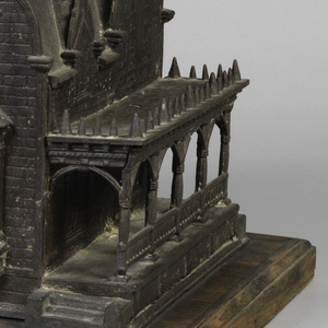 Large metal house, meant to look like brick, with pointed arches and colonnaded side verandas, on a wooden base.