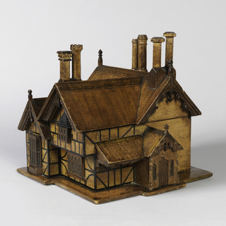 Tea caddy in the form of a nineteenth century Gothic-Tudor style half-timbered house with numerous chimneys, the roof lifting to reveal 2 tea caddies and one glass mixing bowl.