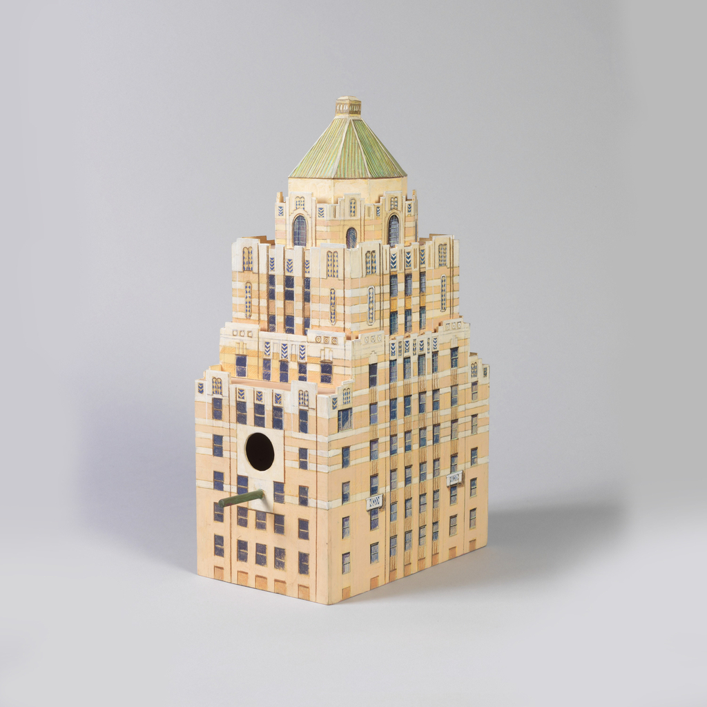 Modeled and painted in beige and pinkish beige replicating the tower of the Carlyle Hotel in New York, with a hole in center and wood peg below for the birds.
