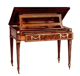 Rectangular form, two shades of mahogany, solid and veneer, on four square tapering legs with horizontally ribbed bronze inlays, square bronze cuffs, acorn feet. Hinged table top with bronze edging and automatically emerging book-rest can be tilted and raised to various levels. One wide drawer in table skirt with ribbed bronze border and two bronze swag handles contains sliding leather-covered writing surface over three inner rear drawers and two sliding covered drawers in front, one of which is compartmented and can be pulled out through side of large drawer. Above each leg on skirt, a square cuff, three vertical grooves and a rosette; bronze beading frames central panel on each side. Horizontal splits through top in four places, badly scratched in upper left corner, other minor scratches, missing beading, missing pieces of wood.