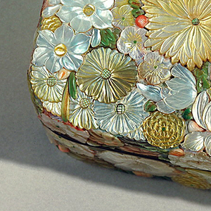 "Rectangular box, with rounded corners, of wood. Sides and tops covered with applied flowers carved in mother-of-pearl and tinted ivory. Silver bands around edge of box and cover. Inside bottom ""nashiji"" (pear ground) lacquer."