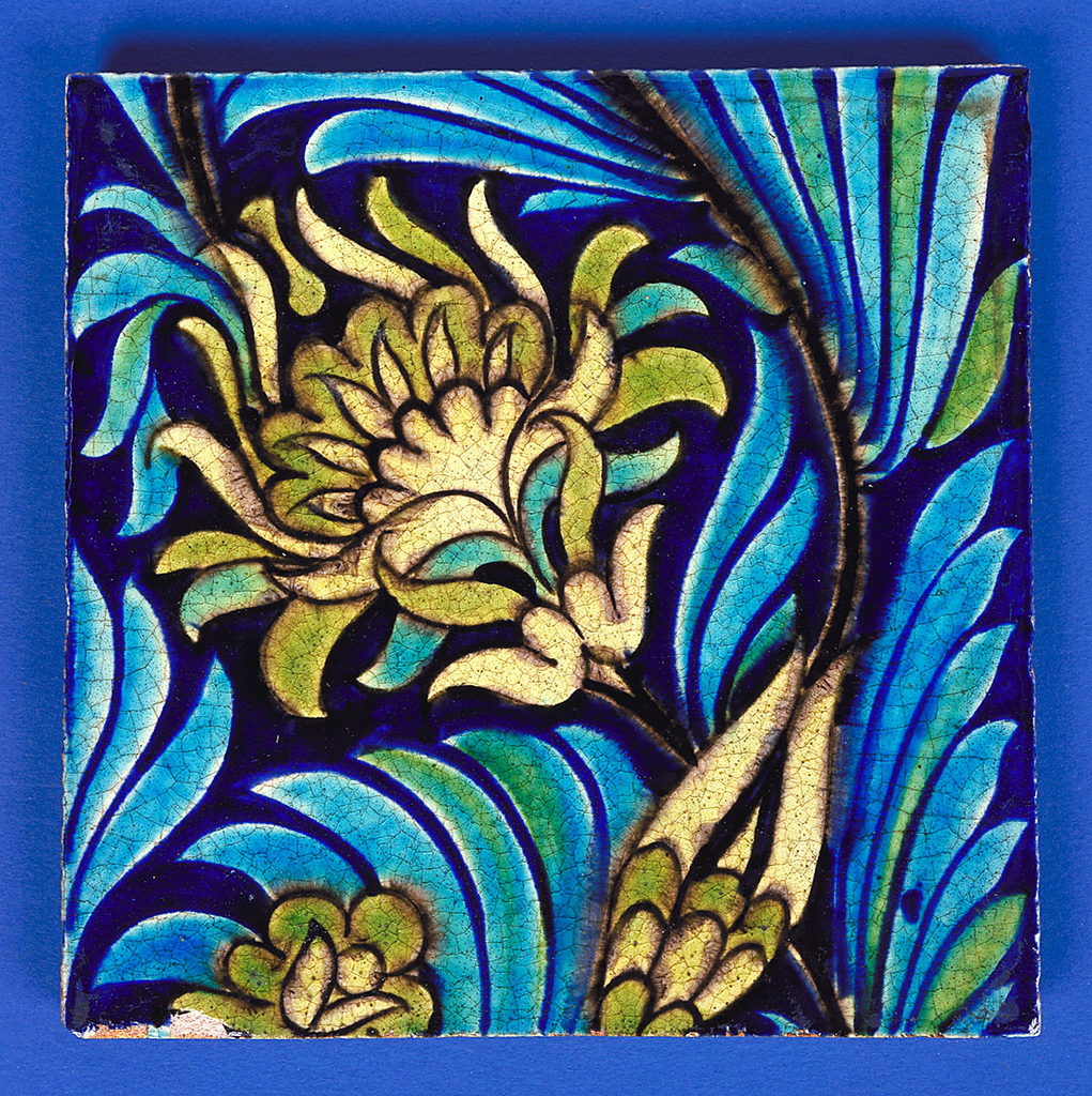 Square tile of buff clay with grogg added. On royal blue ground diagonally set conventionalized flower in pale greens outlined with black and turquoise leaves. Part of large design.