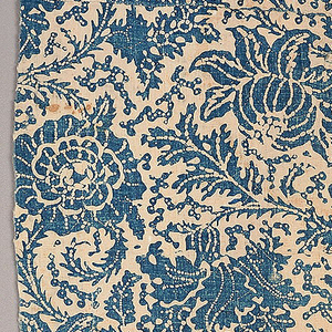 Length from a quilt, of white hand-woven cotton resist printed in blue. Design of ascending curving vine with large flower heads and branching foliage; the leaves are deeply indented, with spiny stems. Lined with bands of white dimity alternating with blue striped cotton.