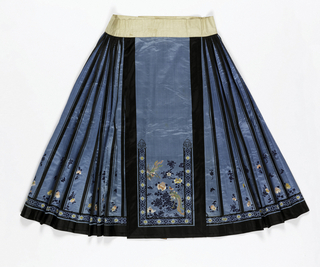 Blue silk satin skirt embroidered in colored silks with a design of flowers and birds; trimmed with black satin bands and black silk braid. Waistband of white linen lined with pink silk woven with a fret pattern. The skirt is made in two parts designed to wrap around the body, with straight panels in the front and back and pleated sections at each side.
